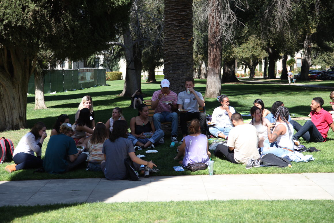 Conference participants in conversation on Bekins Hall's front lawn during lunch.
