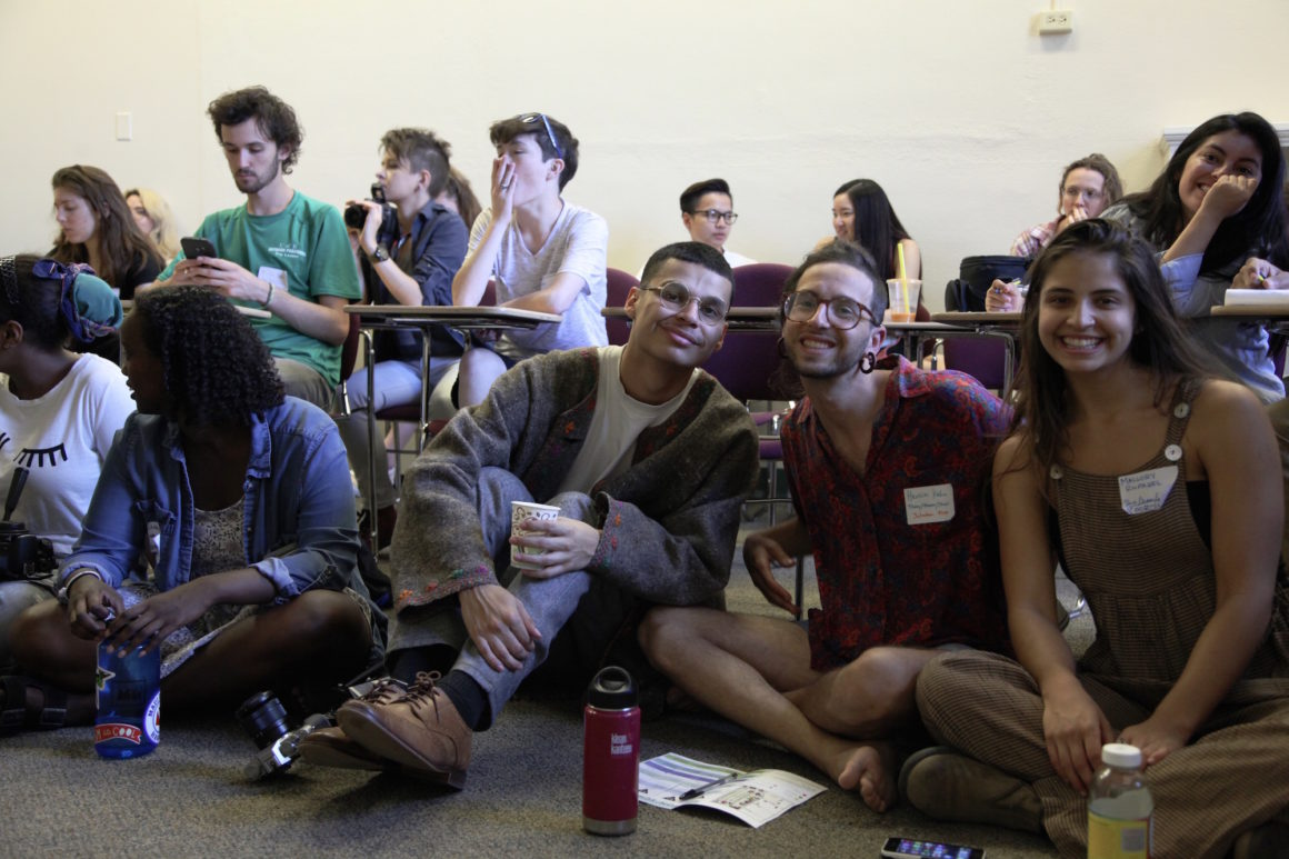Students and alumni, sitting in both desks and on the floor, await a session about grass roots activism.
