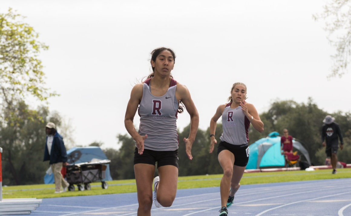Jasmine Ramos, followed closely by Sophie Brooks, hugs the turn of the 200-meter race.